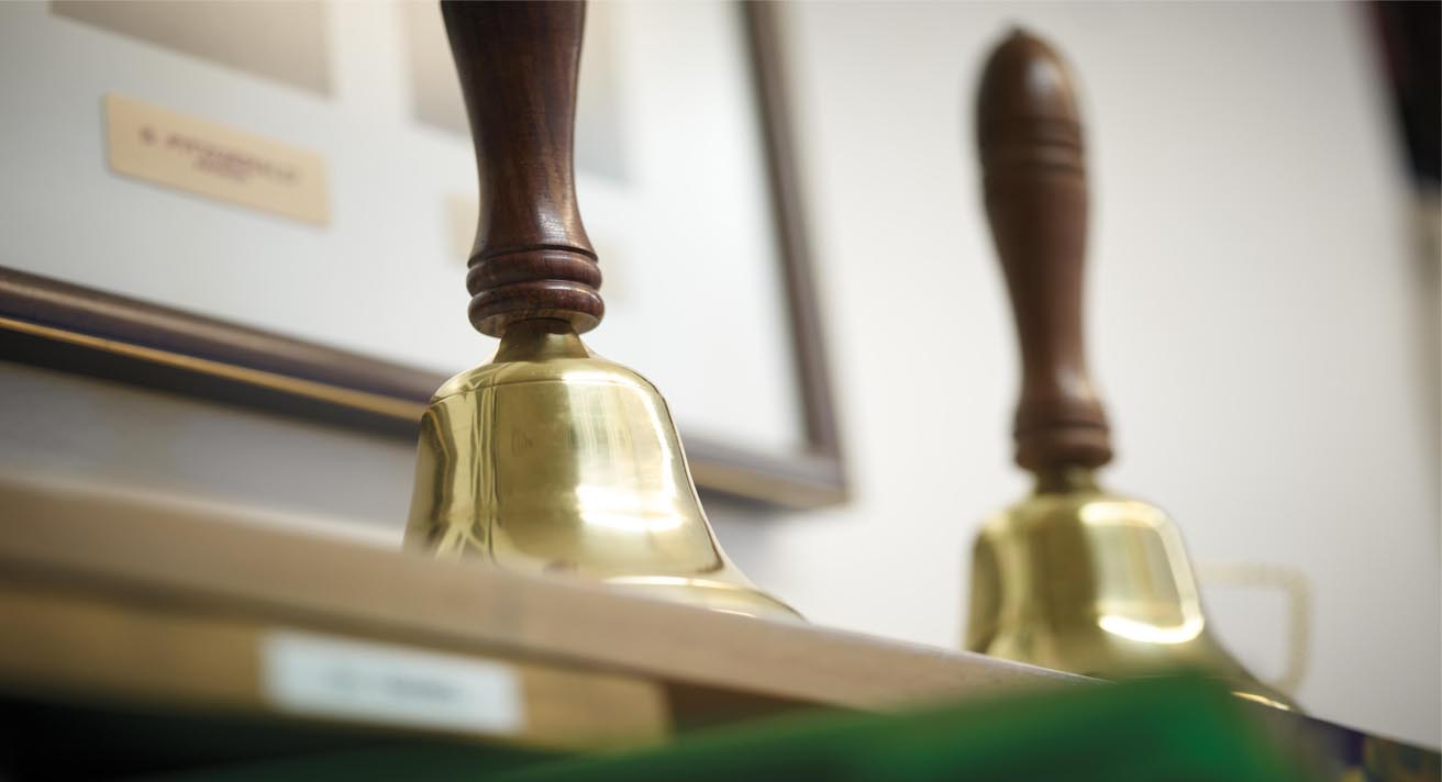 Two old-fashioned hand bells sit on a desk