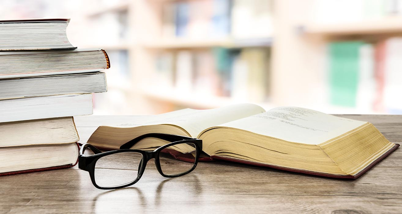 A stack of books and a pair of glasses sit on a desk